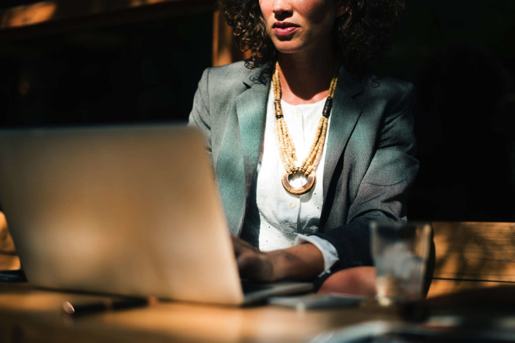 Woman an in a Suit Working on a Laptop