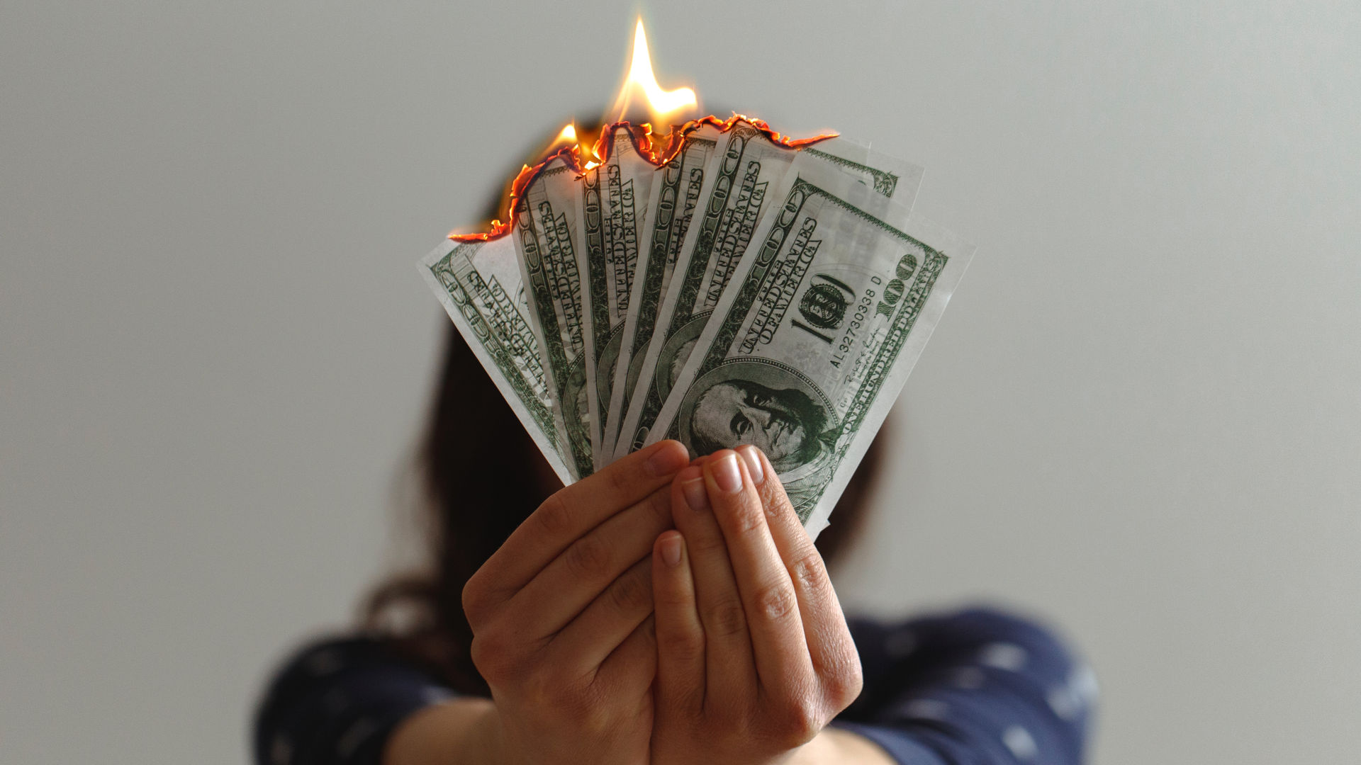 Lady Holding Burning $100 Bills